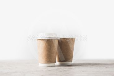 disposable coffee cups on marble table on white