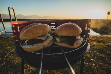 Two tasty burgers on a small metal portable charcoal...