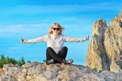 Woman Traveler Relaxing Yoga Meditation sitting on stones...