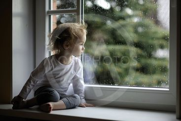 Adorable toddler girl looking at raindrops