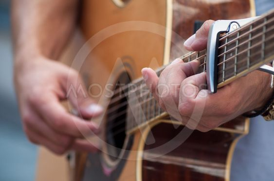 hands of musician on folk guitar in the street