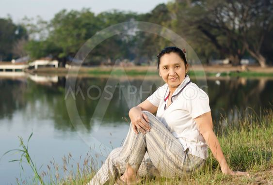 Portrait of smiling woman sitting on green field