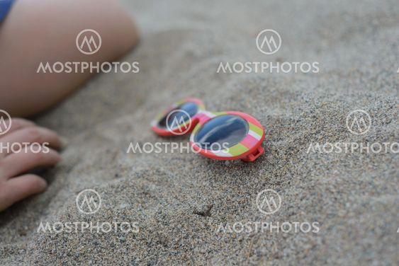 Striped sunglasses in the sand