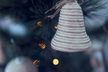 close up of bell hanging from christmas tree with lights on