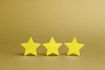 Three golden stars on a yellow background. Quality...