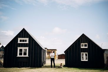 A man in a white shirt between two wooden black houses....