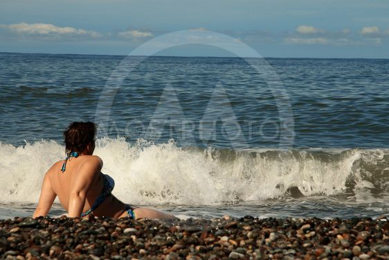 Woman sitting on shore of the sea on the beach
