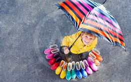 Little kid boy and group of colorful rain boots. Blond...