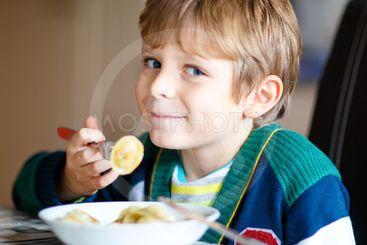 little school boy eating pasta indoor in a canteen.