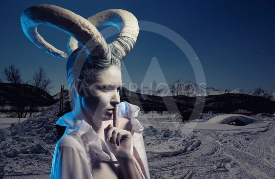Female with goat body-art over winter countryside...