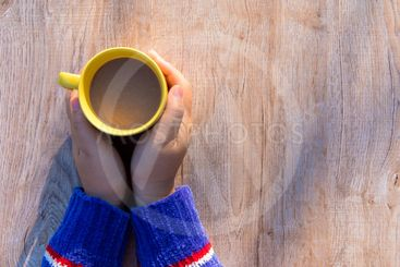 Female hands holding cups of coffee on rustic wooden...