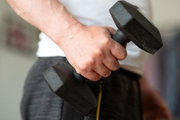 Closeup of a male hand with a dumbbell 5 kg