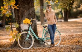 Young woman with bicycle using smartphone in autumn park