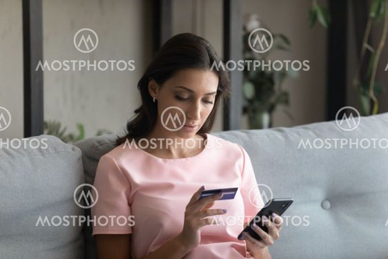 Close up focused Arabian woman holding credit card and...