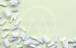 Colorful marshmallow laid out on lime paper background....