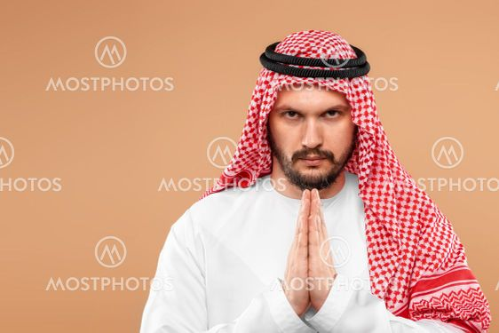An Arab man in national dress is praying on a beige...