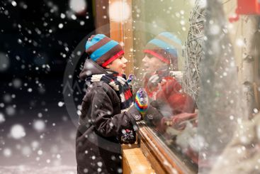 Funny happy child in fashion winter clothes making window...