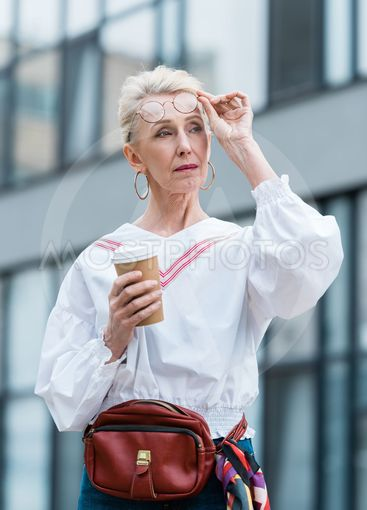 stylish senior woman in trendy glasses holding disposable...