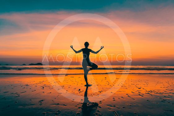 Silhouette young yoga woman on the beach at amazing sunset.