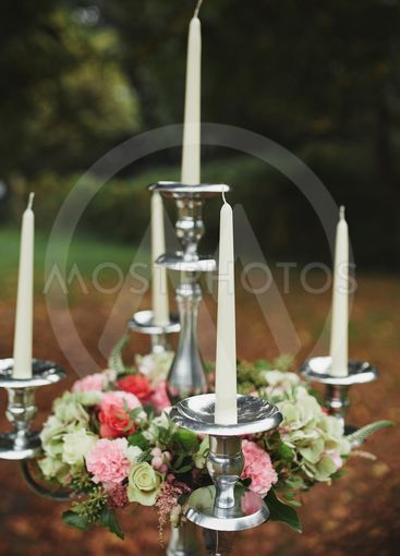Burning candles on bronze candlestick against dark...
