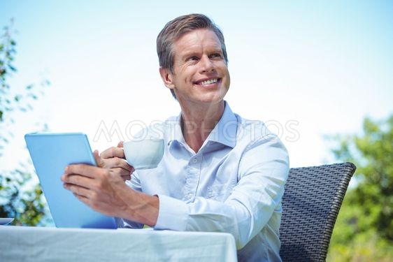 Businessman using tablet with coffee