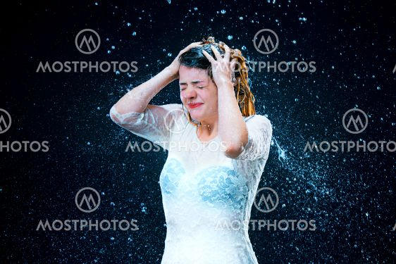 The young girl standing under running water