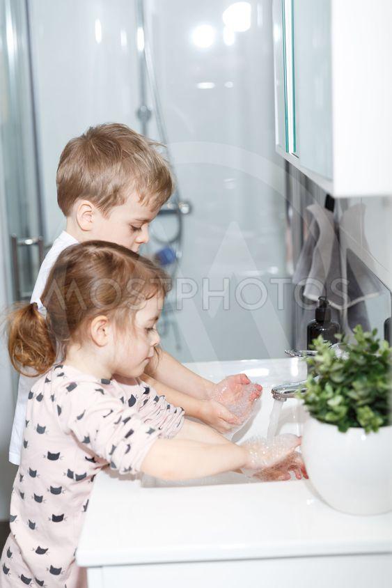Syskon tvättar händerna tillsammans