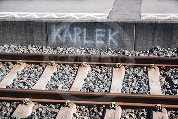 """Plattformskant med texten """"kärlek"""" vid ett järnvägsspår"""