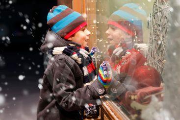 Cute little school kid boy on Christmas market. Funny...
