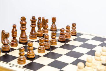 Närbild av schackbräde med pjäser mot vit bakgrund.