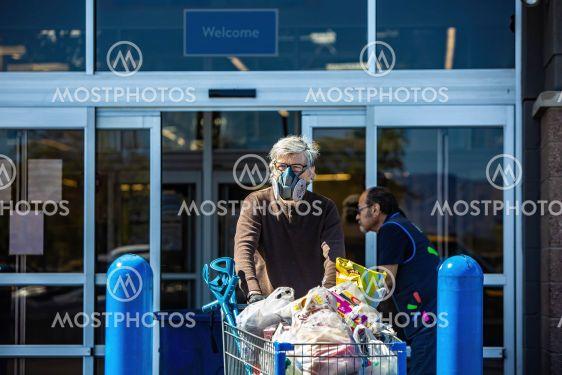 Man wearing ventilator mask to leaving retail grocery...