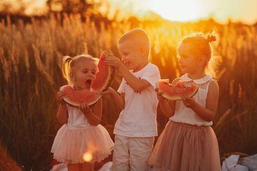 happy kids eating watermelon. Kids eat fruit outdoors....