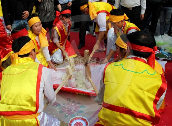 People in traditional costume exam to make round sticky...