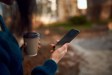 Unknown female holding paper glass of coffee and mobile...