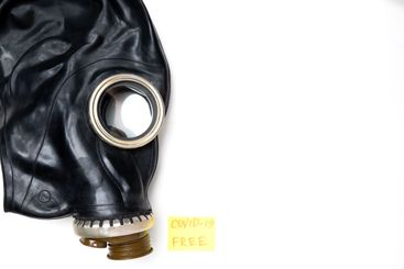 Flat lay. Black gas mask on a white background and a...