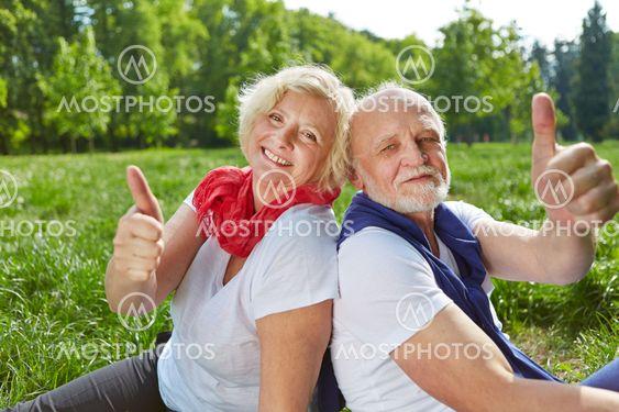 Happy senior couple holding thumbs up