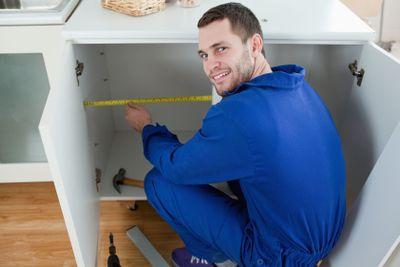 Smiling repair man measuring something