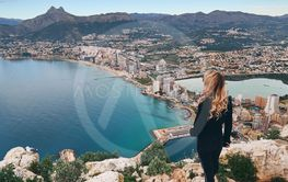 Rear view woman climbed up on peak of Penon de Ifach...