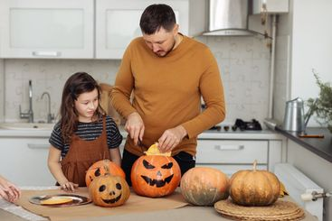 Happy Halloween. father and little daughter carve a...