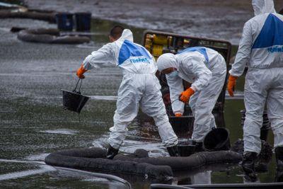Workers scoop crude oil.