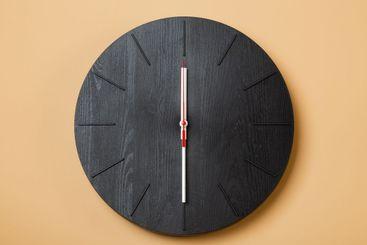 minimalist black wall clocks on brown background