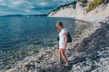 Elderly senior traveling backpacker mature woman tourist...