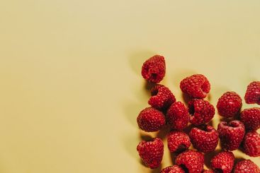 Bunch of raspberries over a clean yellow background