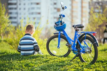 A child sits near his bike at sunset