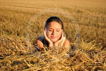 girl in traditional Russian costume resting on a haystack