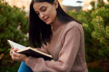 Young female reading paper diary outdoors attentively