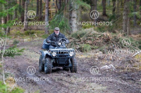 Man kör fyrhjuling på skogsväg