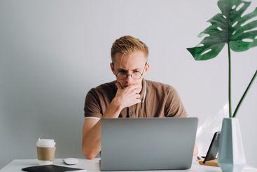 Pensive caucasian man in glasses mobile developer,...