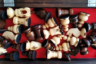 Many chess figures inside wooden box