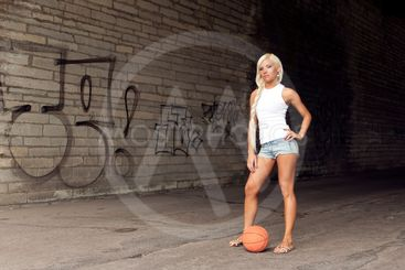 Beautiful blonde girl standing with basketball in the...